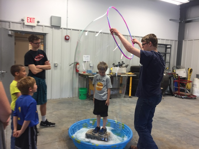 Nate is creating bubbles that stretch over students' heads!