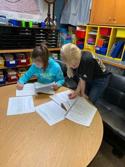 Fourth Graders working hard at collaborating writing summaries.