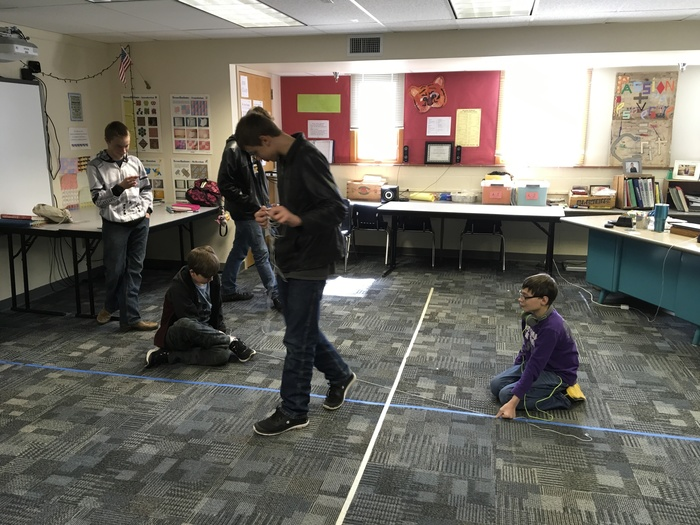 The students use their string to show where the line crosses the y-axis and it's slope.